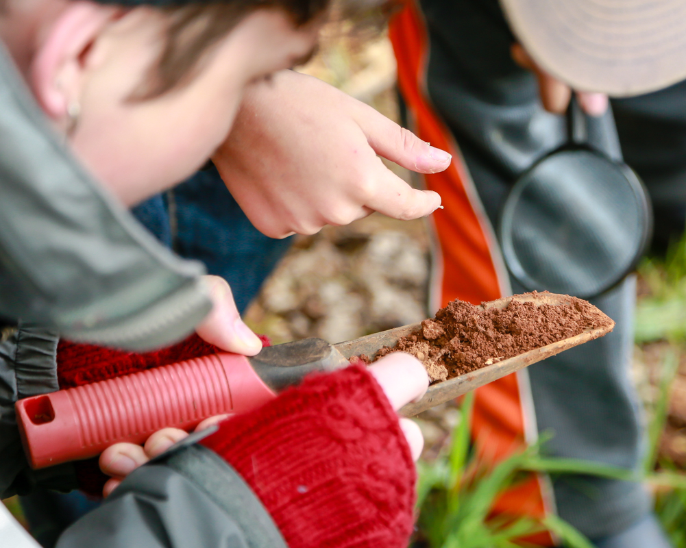 student with trowel full of soil