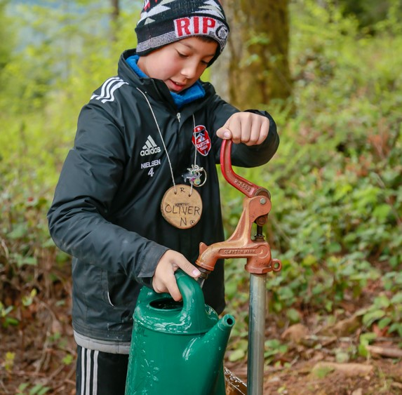 student filling watering can from outdoor pump
